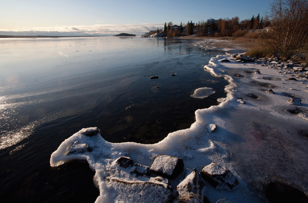 A body of water with a layer of ice along the shore.