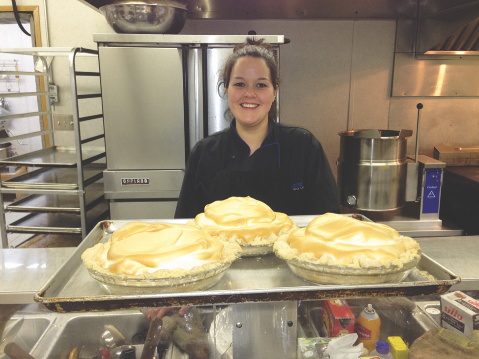 An employee smiling while standing in a kitchen behind a counter with fresh pies on it.