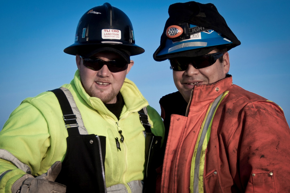 Two workers standing next to each other outside in hard hats, protective sun glasses and safety gear. A clear blue sky can be seen in the background.