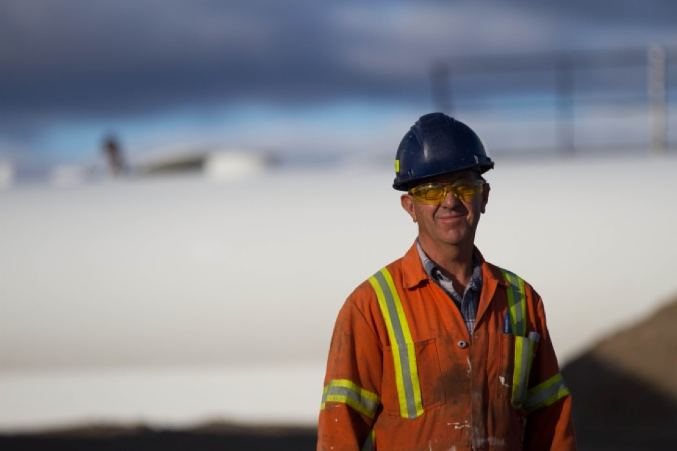 A worker wearing safety gear stands in front of a snowy work site.