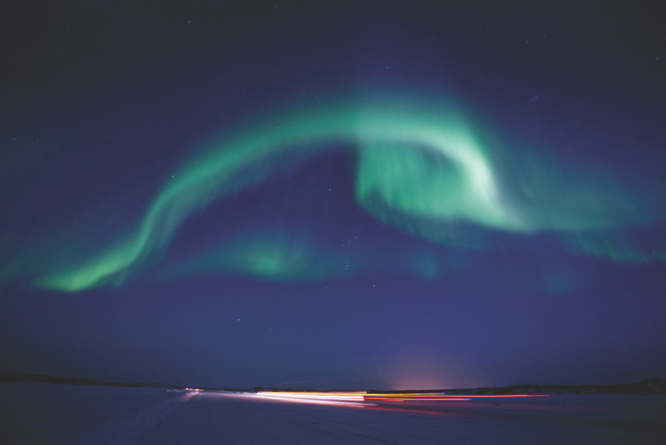 Light green wisps of northern lights dancing in the night sky